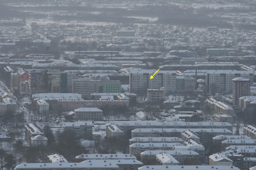 View of Yuzhno-Sakhalinsk from the ski-slope at Gornii Vozdukh.  Our apartment is indicated by the yellow arrow.