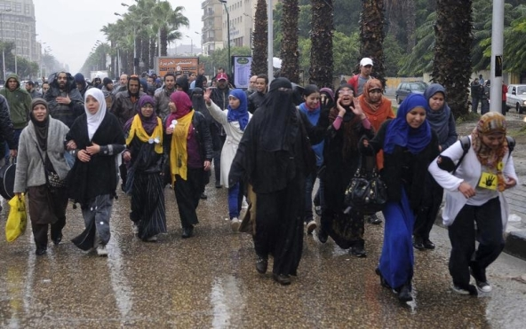 Supporters of the Muslim Brotherhood and ousted Egyptian President Mohamed Mursi walk in the rain during a protest at Al-Haram street, in Cairo December 13, 2013. With many of its male members jailed, Egypt's besieged Muslim Brotherhood is calling up an unlikely reserve force against the army-backed government in the conservative Arab country. At more and more protests, female members of the Islamist movement can be seen taking on security forces mounting one of their fiercest crackdowns against the group. REUTERS/Stringer (EGYPT - Tags: POLITICS CIVIL UNREST) - RTX16HBF