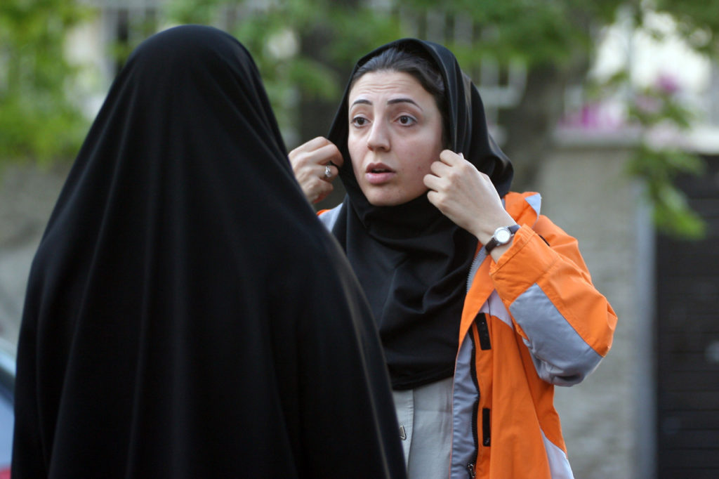 TEHRAN, IRAN - APRIL 22: An Iranian policewoman (L) warns a young woman about her clothing and hair during a crackdown to enforce Islamic dress code on April 22, 2007 in Tehran, Iran. Police issued warnings and conducted arrests during an annual pre-summer crackdown, which was given greater prominence this year, according to officials. (Photo by Majid Saeedi/Getty Images) *** Local Caption ***
